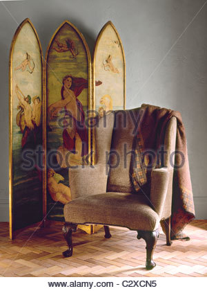 Upholstered wingback armchair in front of hand-painted screen - Stock Photo