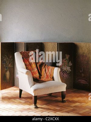 White fabric covered armchair with orange and red throw draped over arm - Stock Photo