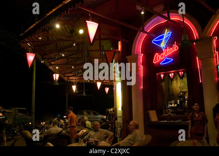 Tourists and local people are enjoying cocktails and food at a modern and colorful corner restaurant in Phnom Penh, - Stock Photo