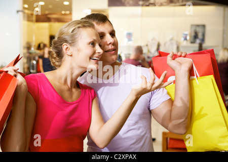 A woman showing something to her husband in supermarket - Stock Photo