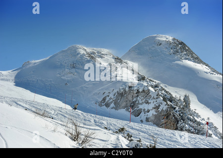 A skier at the Vogel Ski Centre on the Orlove glave - Zadnji Vogel piste in the Triglav National Park of Slovenia - Stock Photo