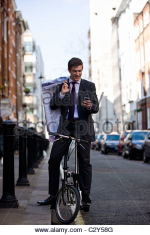 A businessman on his bicycle, looking at his phone - Stock Photo