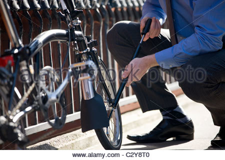 A businessman pumping up the tires on his bicycle - Stock Photo