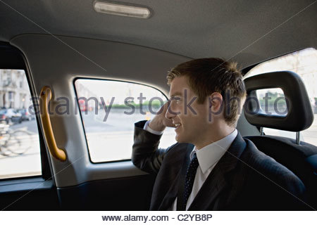 A businessman in a taxi, talking on his mobile phone - Stock Photo