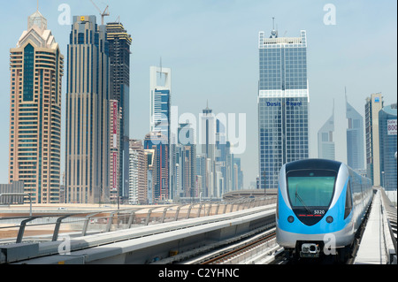View of Dubai metro train and office towers in financial district of Dubai United Arab Emirates UAE - Stock Photo