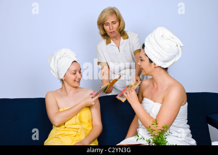 A senior woman worker in a spa resort giving magazines to two women who sitting on couch and waiting for treatments - Stock Photo