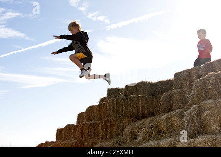 2 brothers jumping off of bales of hay during Halloween, - Stock Photo