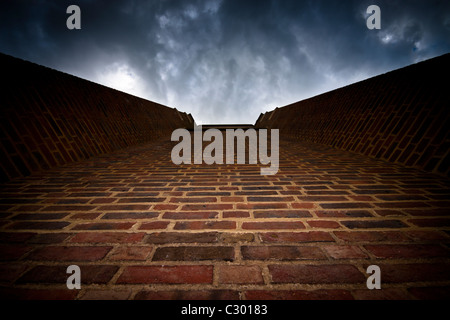 Abstract photo of brick wall and dramatic dark sky - Stock Photo