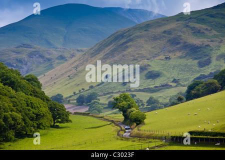 Car motoring along winding road through picturesque valley at Llanfihangel, Snowdonia, Gwynedd, Wales - Stock Photo