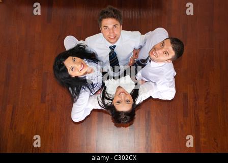 Top view of team of happy united business people standing in a huddle on wooden floor - Stock Photo
