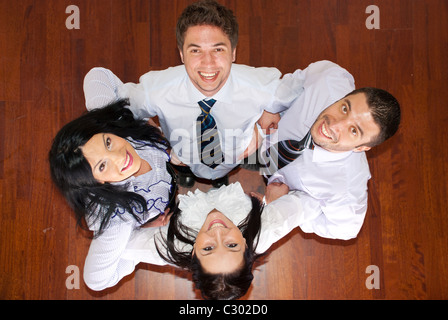 Top view of laughing four business people in a huddle - Stock Photo