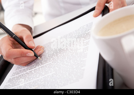 Close-up of businesswoman's hand holding pen over document with white cup near by - Stock Photo