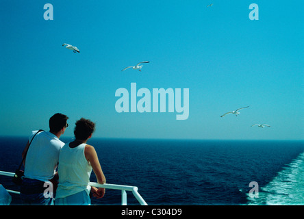 couple enjoying the sunshine on the rear deck of a cross Channel ferry - Stock Photo