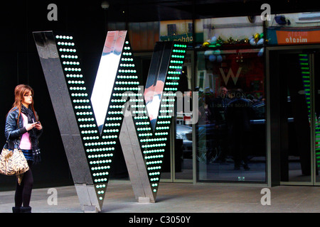 Woman walks past the entrance of the newly opened W Hotel in Leicester Square, London - Stock Photo