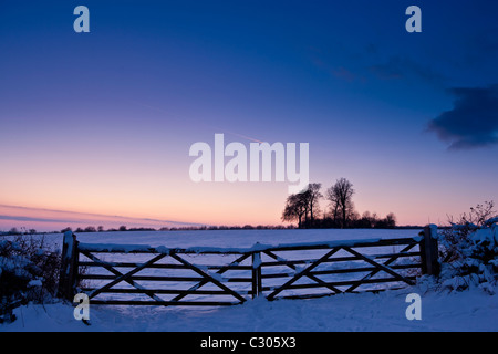 Farm gate in traditional snow scene in The Cotswolds, Swinbrook, Oxfordshire, United Kingdom - Stock Photo