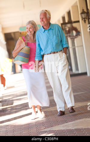 Happy senior man and woman couple holding hands and walking through a sunlit shopping mall - Stock Photo