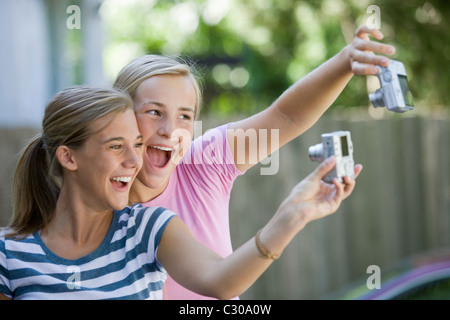 Teen girls taking picture with digital cameras of each other - Stock Photo