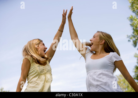Teen girls celebrate winning by jumping in air and doing a high-five - Stock Photo