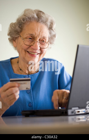 Smiling senior woman using credit card and laptop - Stock Photo