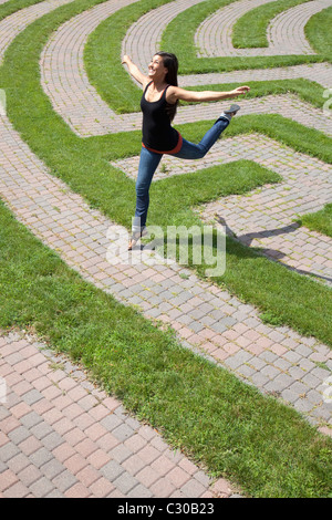 Beautiful young Asian woman playfully jumps over the grass boundary of a park labyrinth. Vertical shot. - Stock Photo