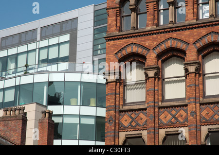 Glass and steel commercial architecture in stark contrast to elaborate brickwork.Manchester city centre. - Stock Photo