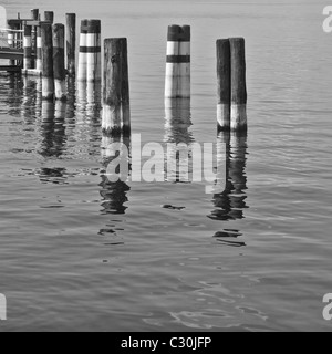 Poles for boats nearby a pier at Iseo Lake in Italy. - Stock Photo