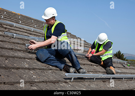 Two men fitting rails for solar pv panel attachment to house roof Wales UK - Stock Photo
