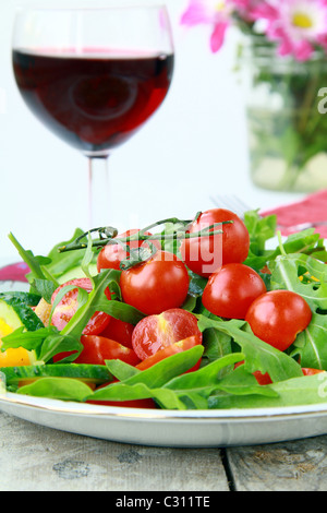 salad with arugula and cherry tomatoes with a glass of wine in the background - Stock Photo
