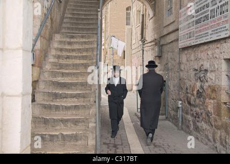 Orthodox jews walking in the Mea Sharim area of Jerusalem, Israel - Stock Photo