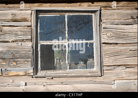 American pioneer, hand-hewn log cabin, with old bottles on the window sill in Ancho, New Mexico. - Stock Photo