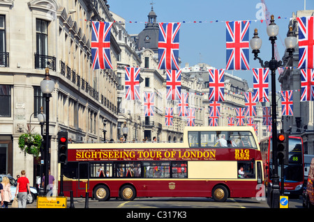 Sightseeing tour bus in Regent Street London with Union Jack flags - Stock Photo