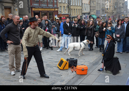 A street performer entertains tourists on the Royal Mile in Edinburgh's Old Town. - Stock Photo