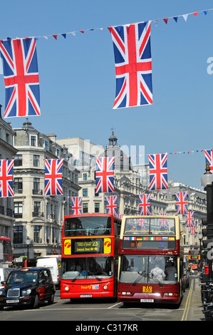 Taxi with London bus alongside open top tour bus in Regent Street London - Stock Photo