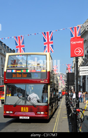 Regents Street scene in London open top sightseeing tour bus beside Carnaby Street signs & union jack flags strung - Stock Photo