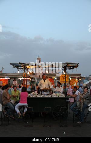 people enjoying food at dusk in Marrakesh main square - Stock Photo