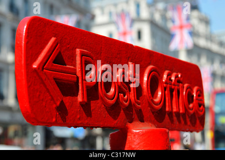 Red Post Office arrowed direction sign on top of post box union jack flags in Regent Street West End London England - Stock Photo