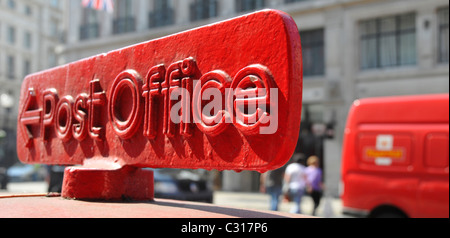 Post Office arrowed direction sign on top of red post box with Royal Mail van beyond Regent Street West End London - Stock Photo