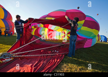 Two men holding the balloon open as it fills up with air. Albuquerque, New Mexico, USA.