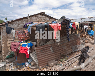A family's wash hangs to dry off of the roof of a portion of their simple home in Totonicapan, Guatemala. - Stock Photo