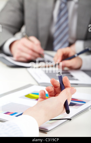 Close-up of businesswoman's hand with pen over document - Stock Photo