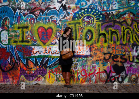 A beautiful woman has her photo taken in front of the John Lennon Wall - Stock Photo