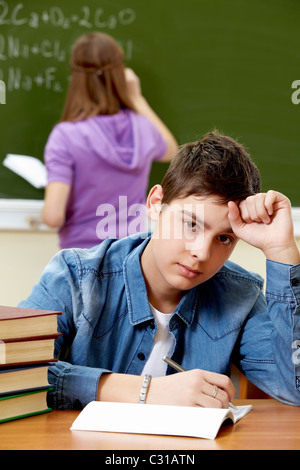 Portrait of smart guy looking at camera in working environment - Stock Photo