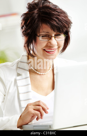 Portrait of middle-aged female typing and looking at laptop display