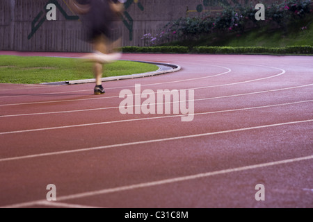 It is a man running in play gorund lanes on a track - Stock Photo