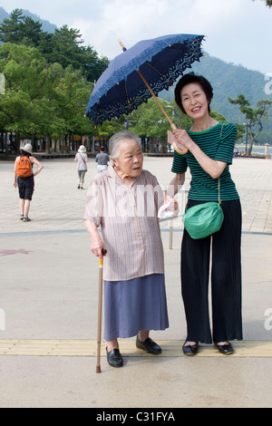JAPANESE WOMEN ON MIYAJIMA ISLAND PROTECTING THEMSELVES FROM THE SUN WITH AN UMBRELLA, JAPAN - Stock Photo