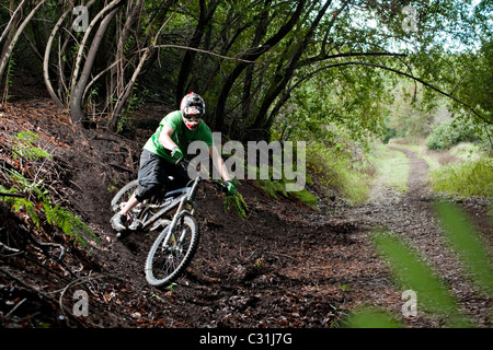 A young man rides his downhill mountain bike on Knapps Castle Trail, surrounded by beautiful scenery in Santa Barbara, - Stock Photo