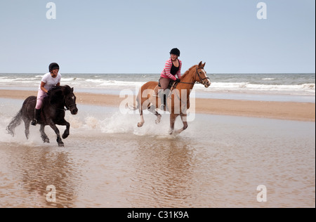 Riding horses on Holkham Beach, North Norfolk, UK - Stock Photo