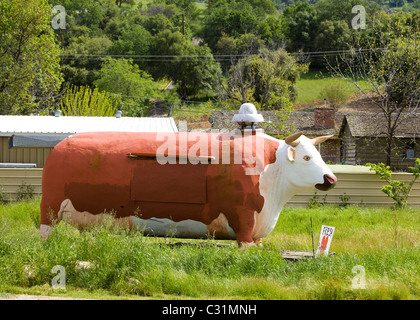 A large BBQ smoker in the shape of a cow sits in rural California - Stock Photo