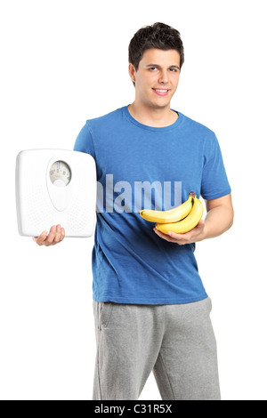 A young male athlete holding a weight scale and bananas - Stock Photo