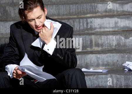 Portrait of thoughtful business man touching his chin and looking at paper - Stock Photo